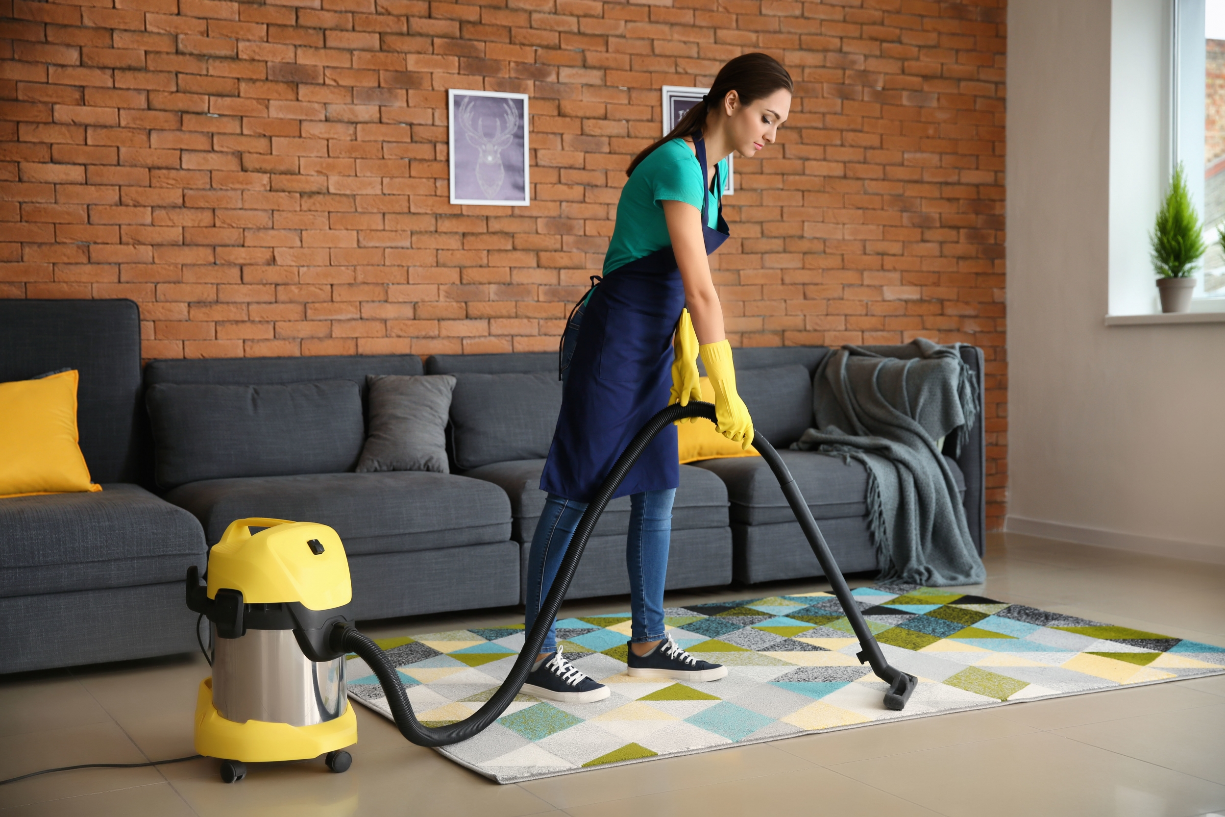 Female janitor hoovering carpet in flat